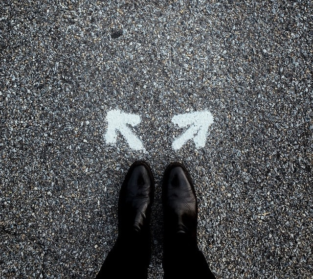 Feet standing before two arrows in different directions (Photo by Jon Tyson on Unsplash)